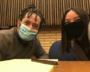CLDC client Eric Jackson (l) with CLDC staff attorney Sarah Alvarez (r) sitting at a wooden tadle with a brick and wood wall in the background. Both are wearing surgical masks.