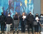 Black Unity members and CLDC lawyers stand in front of a blue and multicolored mural.