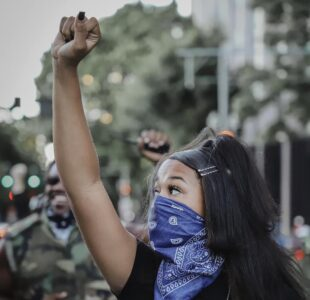 A woman of color stands with her fist raised in the air during a protest.