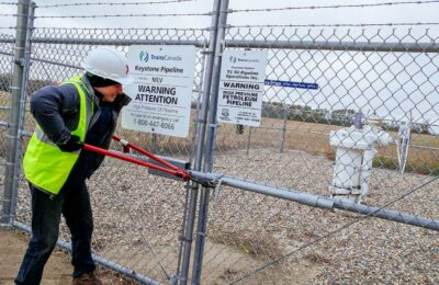Photo of person engaging in direct action by breaking lock to enter TransCanada Keystone Pipeline property.